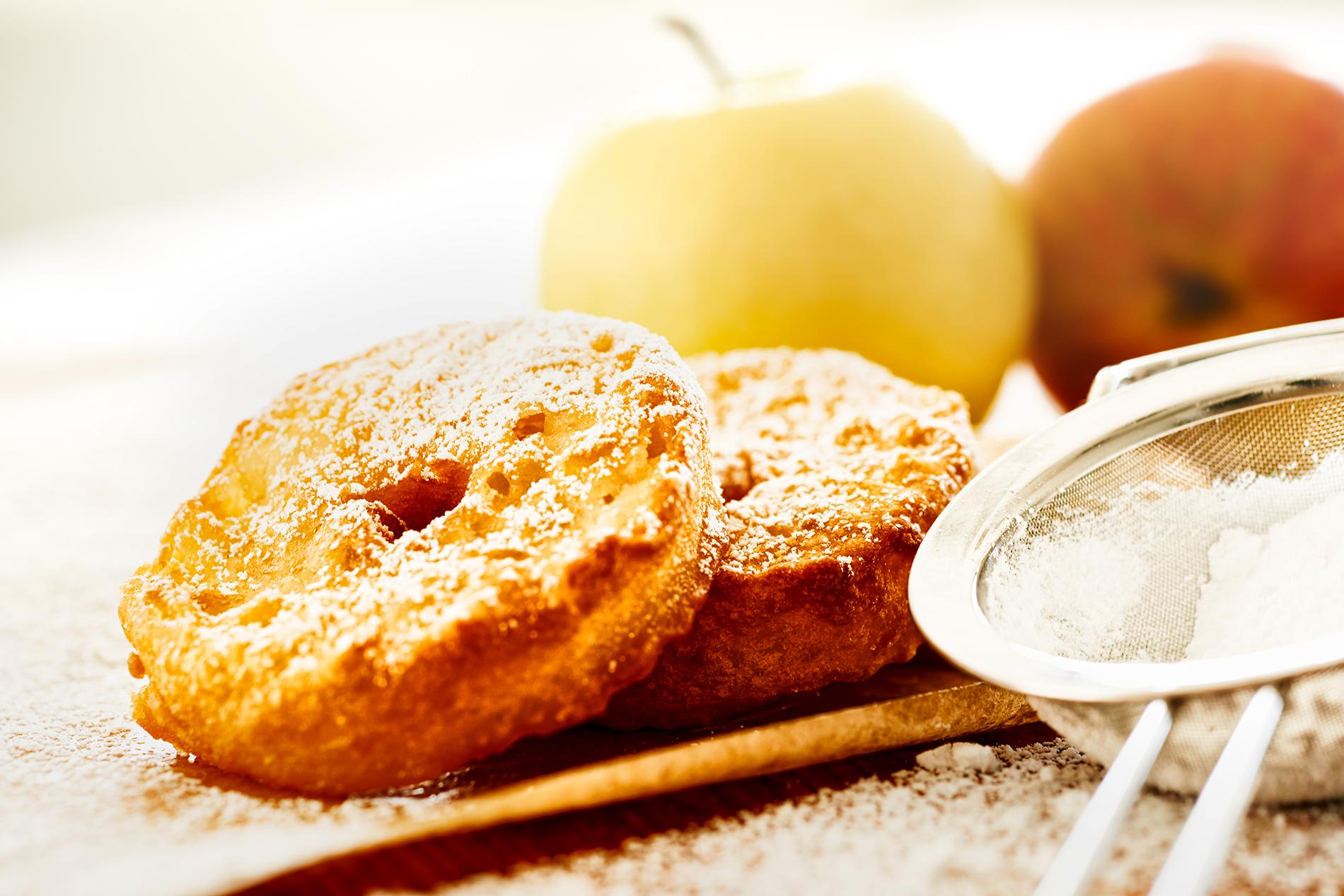 2 Apfelküchle mit Apfel im Hintergrund