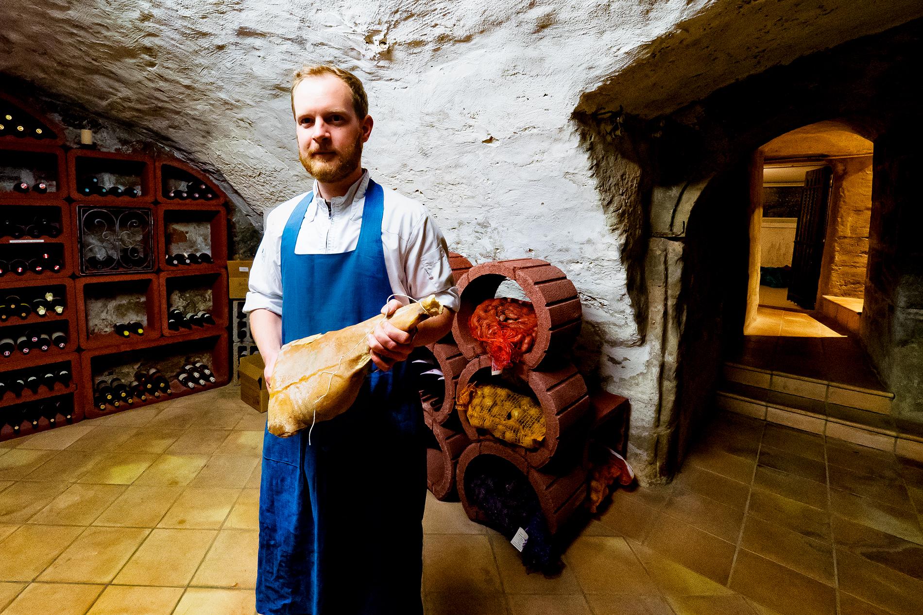 Felix Schneider mit Schinken im Gewölbe des Restaurant Sosein