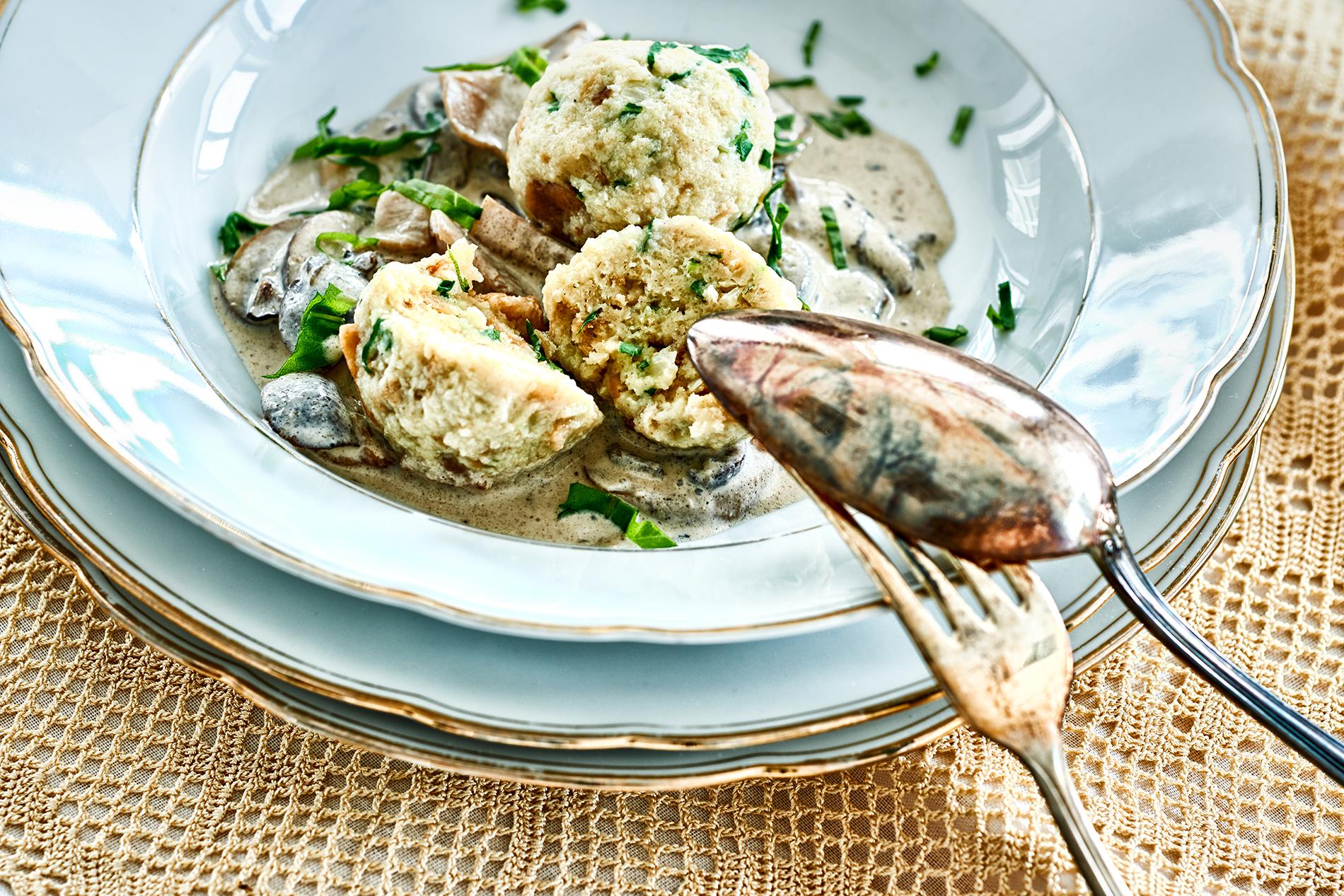 Semmelkloß mit Pilzrahmsoße und Petersilie auf einem weißen Teller mit Besteck