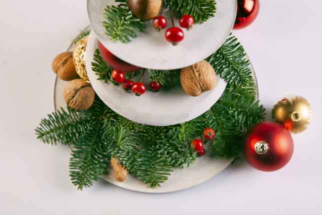 Etagere aus Feinbeton mit Tannenzweigen und Weihnachtskugeln