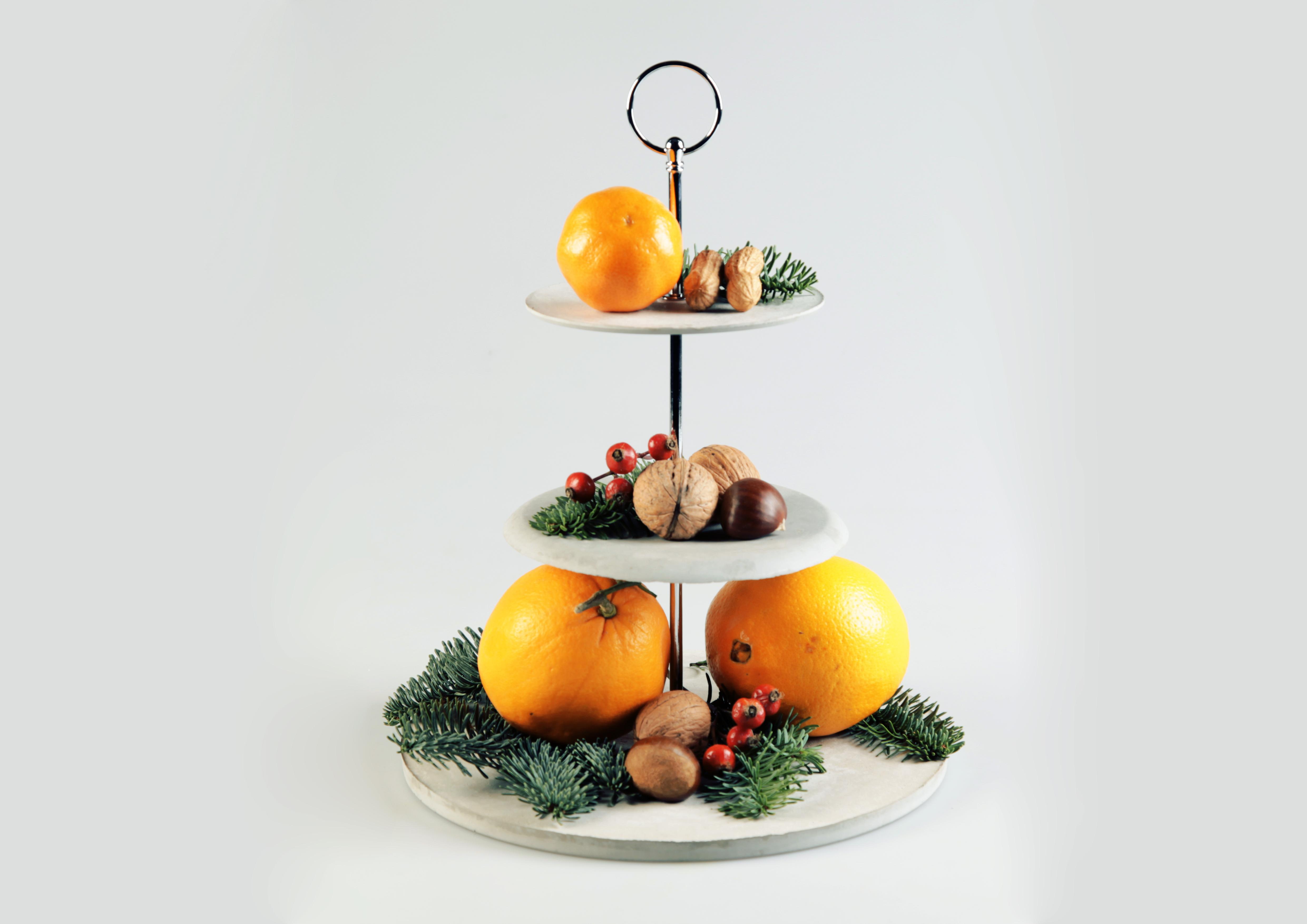 Etagere aus Feinbeton mit Tannenzweigen und Orangen