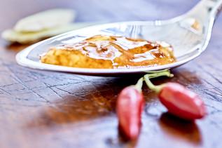 Birnen-Ingwer-Chutney auf einem Löffel mit Chili-Schoten