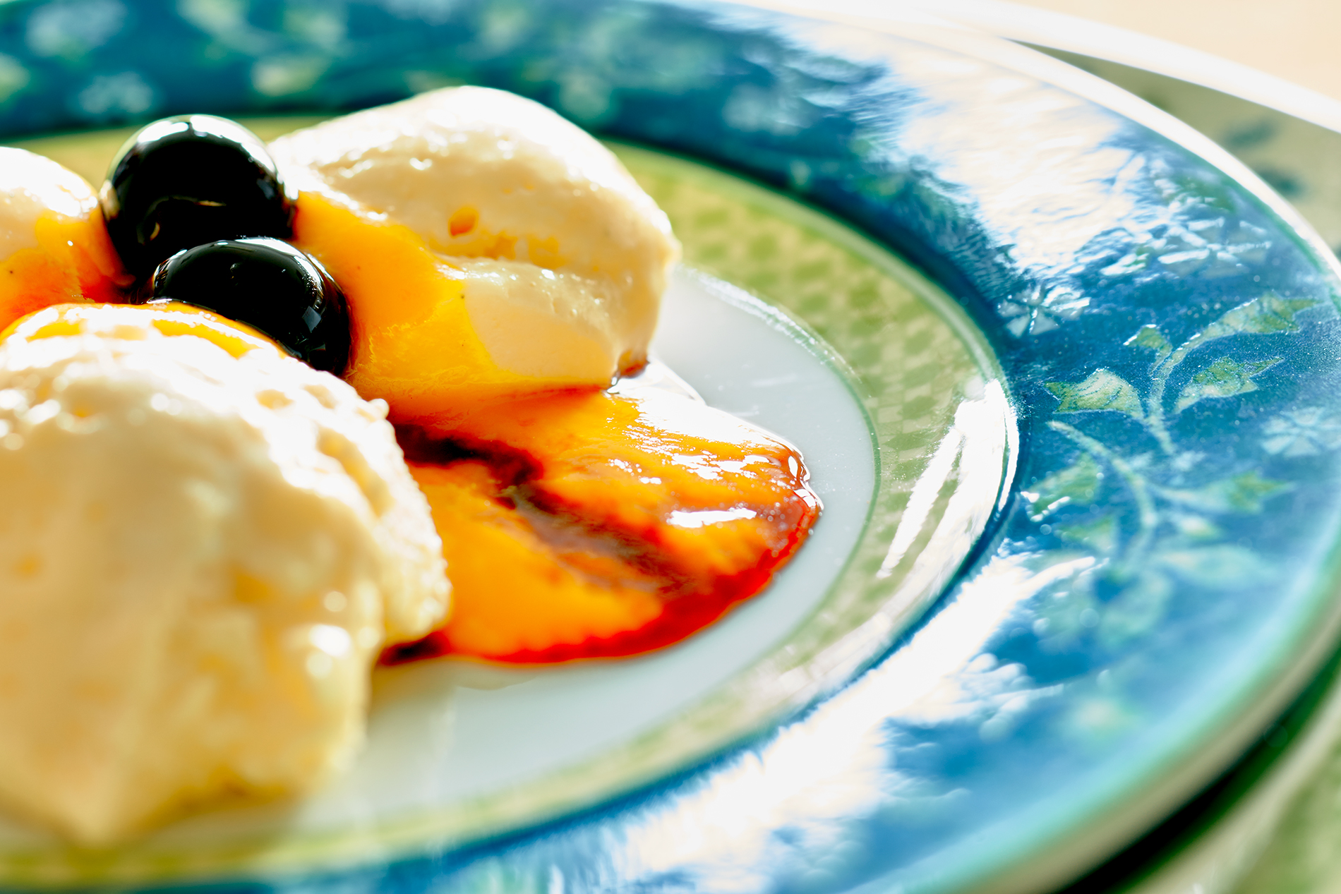 Bayrisch Creme mit Mango-Püree und Amarena-Kirschen auf einem blau-grünen Teller