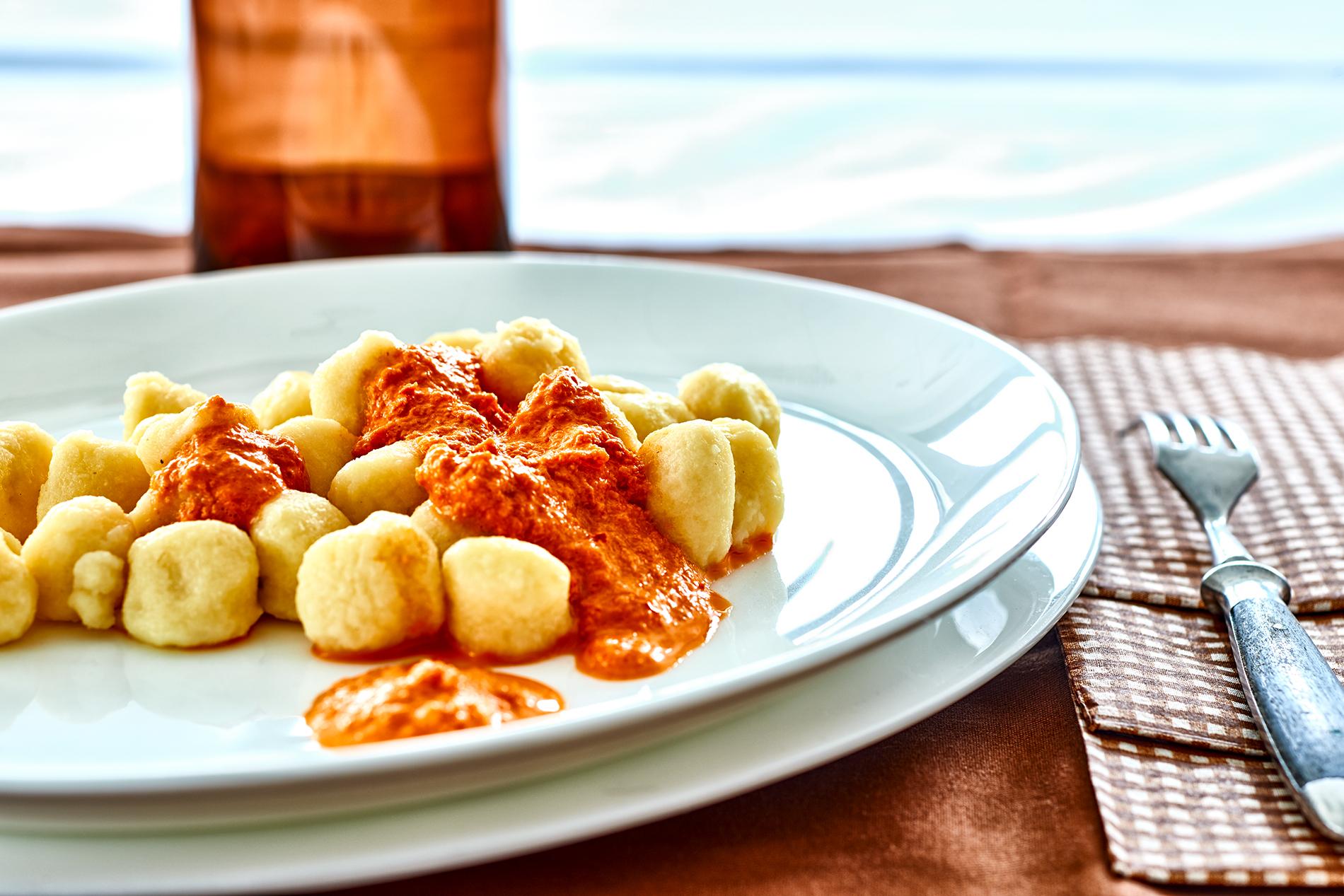Gnocchi serviert auf einem weißen Teller mit Paprikasoße