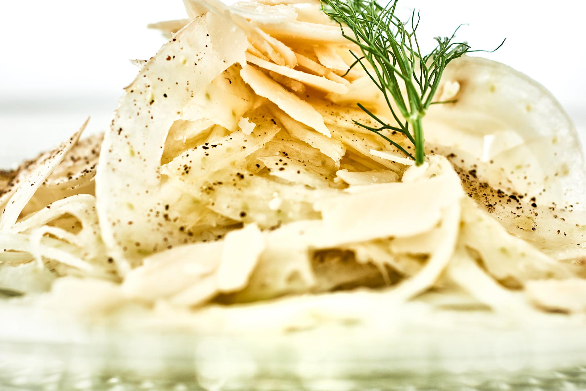 Gehobelter Fenchelsalat mit Zitrone und Parmesan dekoriert mit Fenchelgrün