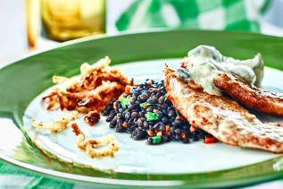 Jägerschnitzel auf einem grün-weißen Teller mit schwarzen Belugalinsen und Kartoffel-Rösti