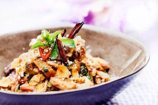 Schüssel mit Nam Tok Gai - thailändisches Gericht mit Fleisch und Chili